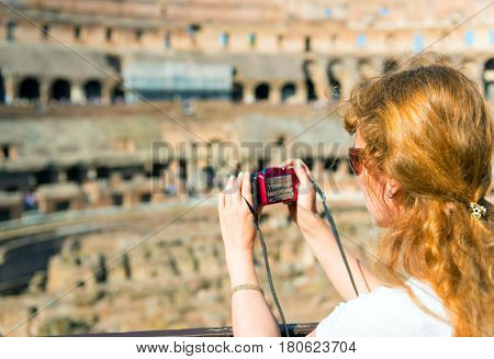 ROME, ITALY - MAY 10, 2014: Young female tourist takes a picture inside the Coliseum in Rome.