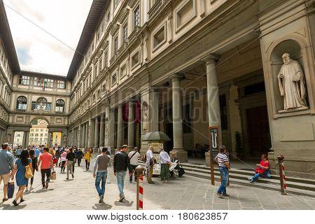 FLORENCE, ITALY - MAY 11, 2014: Tourists walk next to the famous Uffizi Gallery.