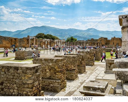 POMPEII, ITALY - MAY 13, 2014: Tourists visit the ruins of city. Pompeii is an ancient Roman city died from the eruption of Mount Vesuvius in 79 AD.