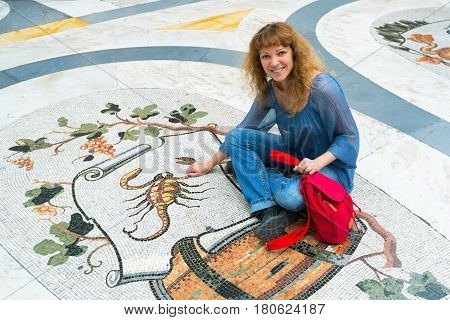 Young female tourist sitting on the image of the Zodiac sign Scorpio in Galleria Umberto I in Naples, Italy