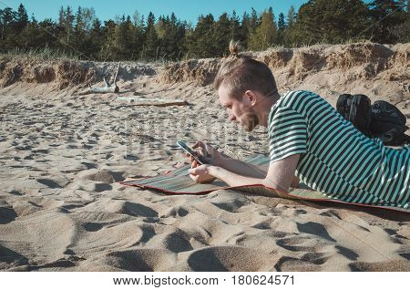 Portrait of stylish young man using smartphone sitting on river coast seaside outdoor. Serious bearded male with hairstyle hold phone and searh. Concept communication modern life. Adventure scouting survival concept.