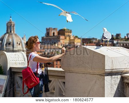 A tourist plays with seagulls on the observation deck at the Vittoriano. In the center of Rome there are many seagulls who are not afraid of tourists.