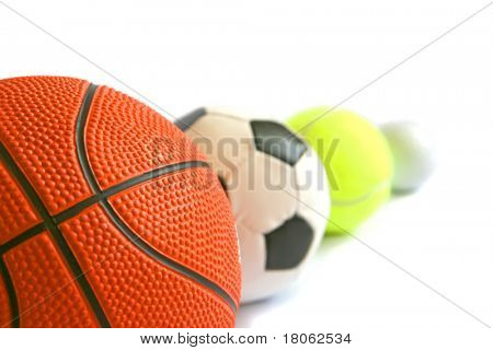 Arrangement of football, basketball, tennisball and golf ball in a row