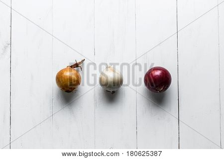 Three bulbs on a white wooden background. White onions, onions and red onions. Top view