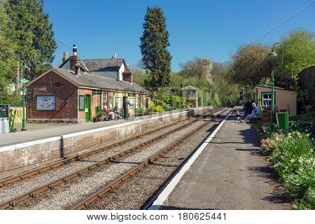 Medstead, UK. 8th April 2017. Bright sunshine on a warm spring day at Medstead station on the Watercress heritage railway line. Some passengers are waiting for a train.