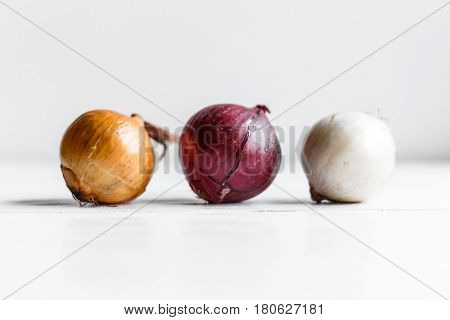 Three bulbs on a white wooden background. White onions, onions and red onions.