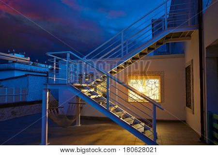 House window light glow in a thunder storm dark sky at sunset dusk with stairs