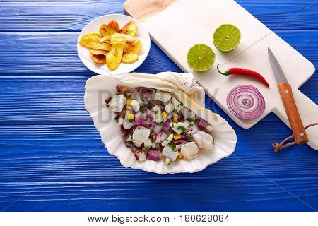 Ceviche peruvian recipe with fried banana and ingredients on wooden blue table