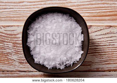 Maldon sea salt flakes in a bowl on a wooden board