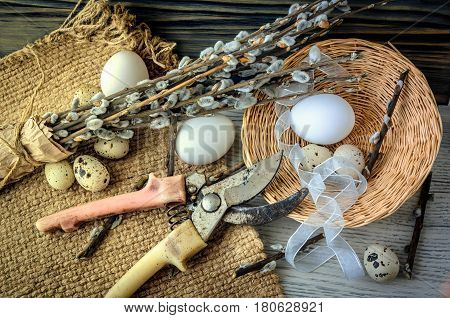 Chicken eggs in a basket on a wooden table and willow branches, rural still life