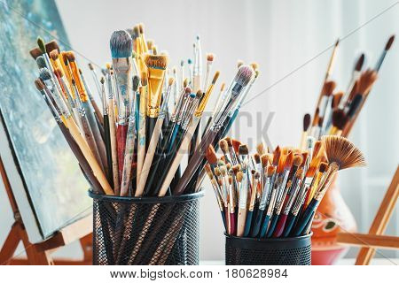 Artistic Equipment In Studio: Wooden Easel,  Paintbrushes, Tubes Of Paint, Palette And Paintings On