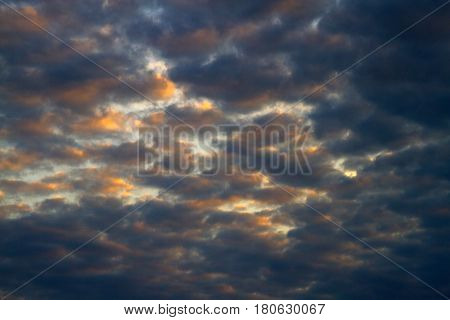 Contrasting Impressionistic looking clouds spatter the blue sky with color near sunset