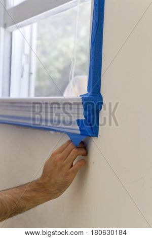 Close up of a young man's hand applying blue painter's tape to a window frame prior to painting an adjoining wall