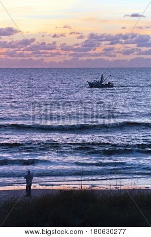Silhouette of a fisherman on the beach and a fishing trawler out on the Gulf of Mexico backlit by a colorful sunset in Indian Rocks Florida
