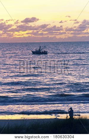 Silhouettes of a fisherman on the beach winding his line and a trawler out on the water backlit by a colorful sunset both ready to head home after a long day of fishing the Gulf of Mexico in Indian Rocks Florida