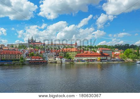 Prague cityscape with a view of Prague Castle and St Vitus Cathedral from Charles Bridge on a sunny summer day.