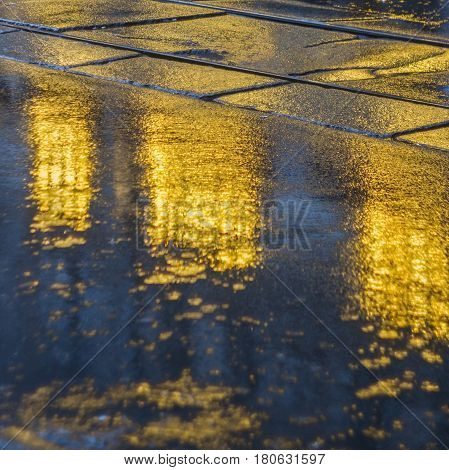 The bright lights of the evening city after rain headlights from the approaching car. View from the pavement level