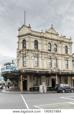 Auckland New Zealand - March 1 2017: Cream white facade of the historic Naval Family Hotel now converted into the hottest strip club of the city: Calendar Girls. Gold on black advertisement.
