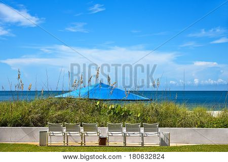 Six White Beach Chairs with a Blue Umbrella out on the Beach