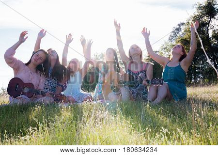 Young Girls Sitting Together in Green Grassy Field Singing and Playing Musical Instruments With Arms Raised up