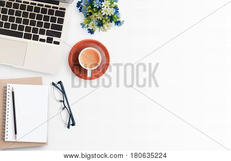 Modern White office workspace with eye glasseslaptop computerpencil and cup of coffee. Top view with copy space.Office supplies and gadgets on workspace.Working desk table concept.