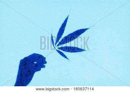 Abstract blue hand and marijuana leaf in fingers image