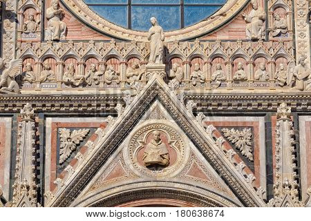 The tympanum of the beautiful marble West facade of the Cathedral Duomo in Siena, Italy