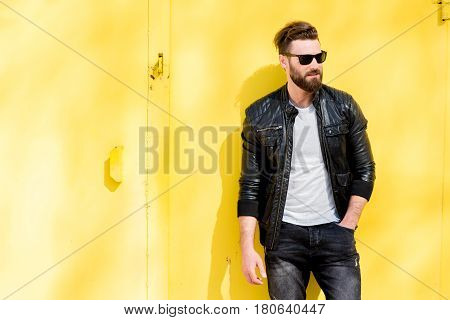 Colorful portrait of a handsome man dressed in white t-shirt, jacket and jeans on the yellow background