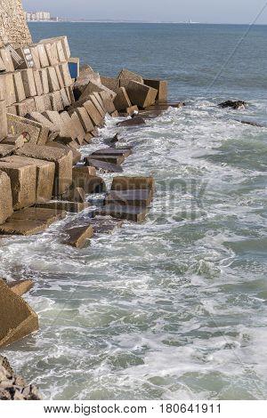Waves hit the rocks on the promenade of the La Caleta beach in Cadiz Spain