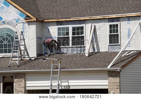JOLIET, ILLINOIS / UNITED STATES - SEPTEMBER 7, 2016: A carpenter replaces the siding on a home in the Wesmere Estates neighborhood of the Wesmere Country Club in Joliet.