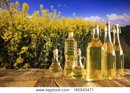 Rapeseed oil on rapeseed field background. Bottles with oil on rustic table. Summer time. Place for typography and logo.