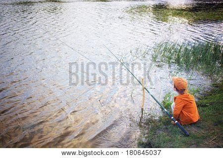 boy with a fishing rod on the river bank. A young fisherman put a fishing tackle on a stick and waits for the beginning of fishing