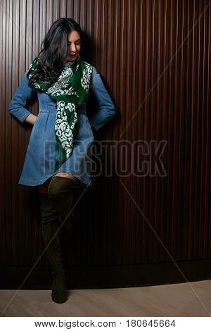 Portrait of Beautiful brunette young oriental beauty female  with black long hair Dressed in a denim dress clothing with Oriental green scarf and oriental jewelry.