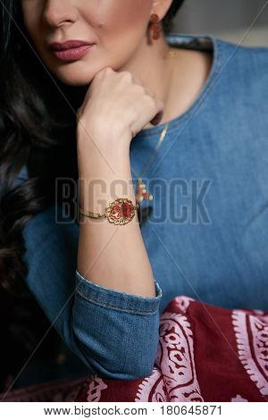 Portrait of Beautiful brunette young oriental beauty with black long hair Dressed in a denim dress clothing with Oriental red scarf and oriental jewelry.