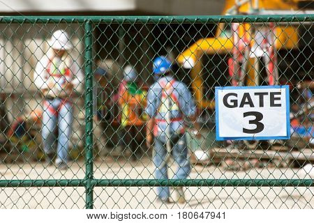 Workers in construction site focus on chain link fence.