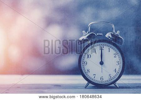 12 o'clock retro clock vintage blue color tone with sun light.