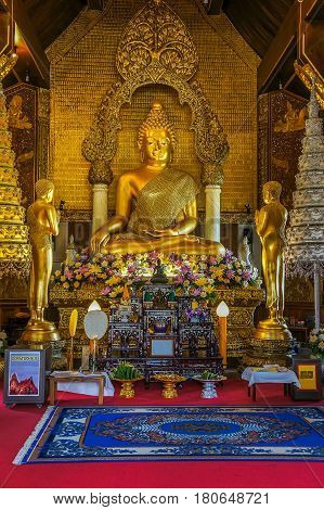 Buddha image with two disciple statues in church of Thailand Buddhist temple.