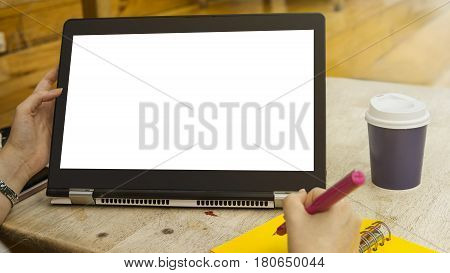 female hand is touching a blank white screen tablet computer gadget and the hand is writing on the yellow notebook with the cup of coffee at the library.