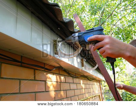 Holder gutter drainage system on the roof. Rain Gutter Holder Installation
