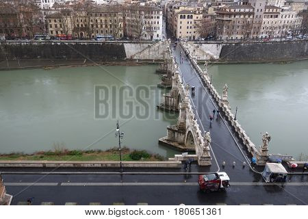 ROME ITALY - MARCH 5 2017: People walking across Sant Angelo Bridge on a rainy day