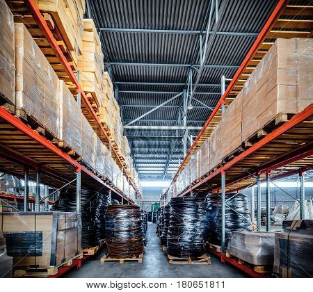 Warehouse with long and high racks. Coiled plastic pipe. Toning the image.