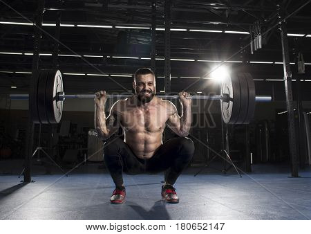 Muscular shirtless sportsman doing the squat exercise in the gym.Functional training.
