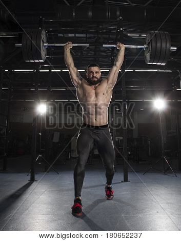 Powerfull muscular shirtless athlete in over head lunge with a heavy weight in modern fitness center.Functional training