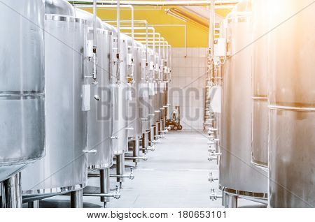 Modern Beer Factory. Steel tanks for storage and fermentation of beer. Sunlight effect