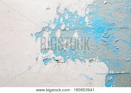 Peeling paint of white and blue colors on the stone texture background.