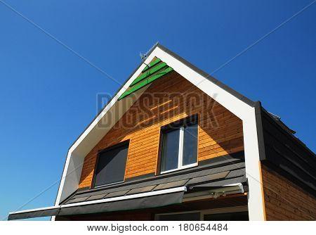 Modern House Exterior Design. New Building House Energy Efficiency Solution Concept Outdoor. Solar Energy Solar Panels Installed on Bitumen Tiled Roof.