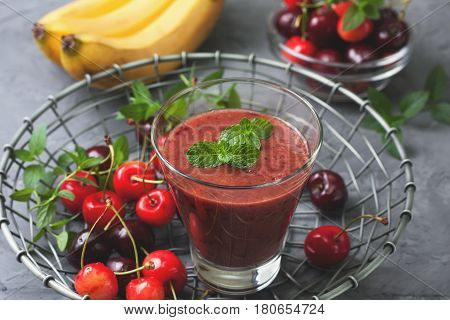 smoothie with cherry and banana in a glass a mixture of sweet cherries on concrete background