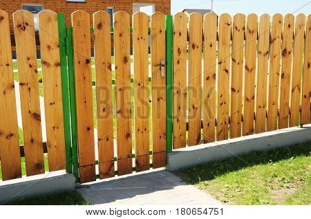 Closeup on wooden gate ( wicket ) and wooden fence detail construction with doorway outdoor. Wooden fencing.