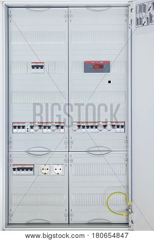 Electrical Cabinet with main breaker and modular circuit-breakers. The Cabinet door is open. All components are covered with protective panels for safety. Visible grounding the green and yellow wire.