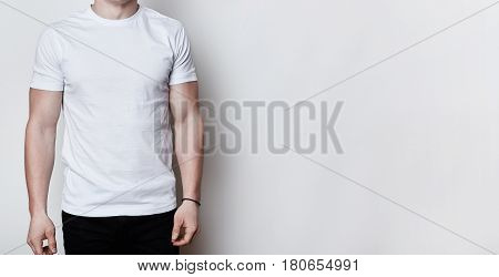 A portrait of a man having athletic body wearing blank white t-shirt standing on white background with copy space for your advertisment. Clothes advertising.T-shirt design and people concept.